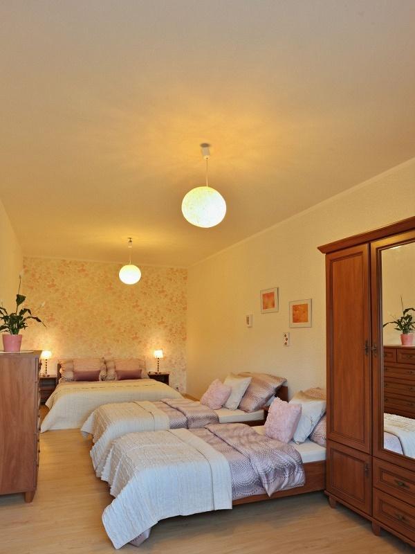 Luxusní ložnice s dvojlůžkem a dvěmi postelemi