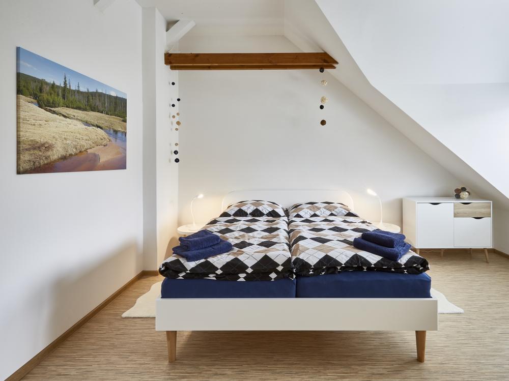 postel v ložnici s arkýřem
