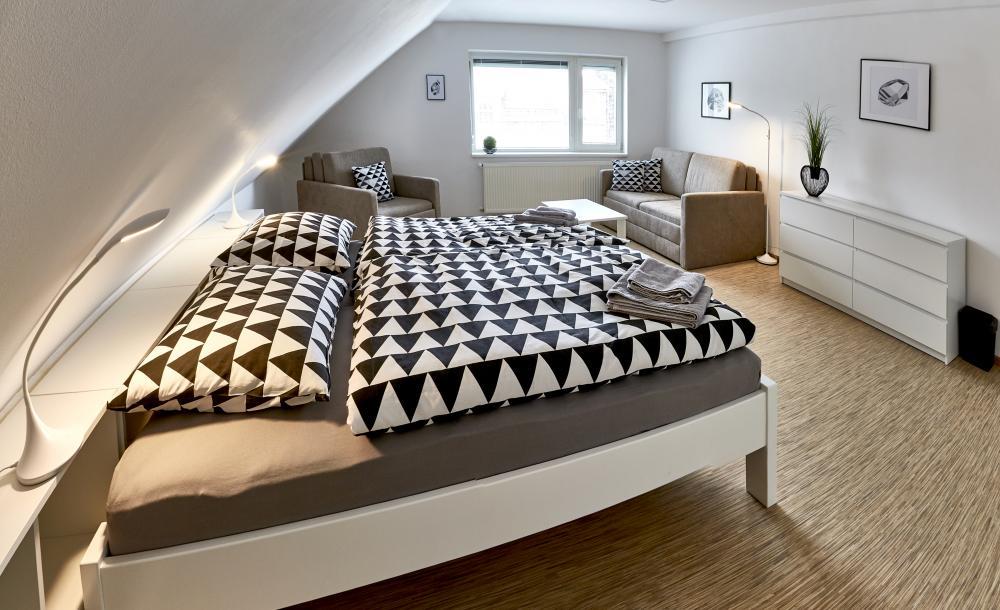 postel v ložnici se šikmým stropem