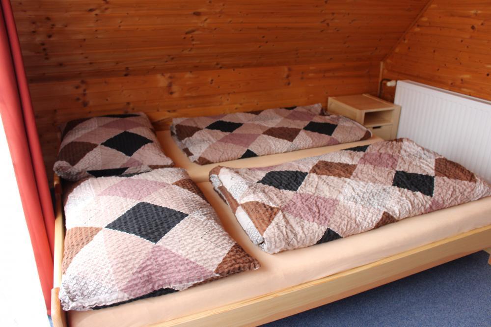 Manželská postel v třílůžkovém pokoji