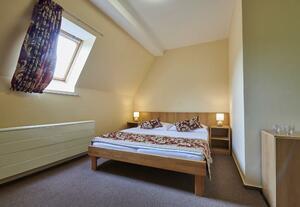 Dvoulůžkový pokoj s manželskou postelí a přistýlkou (východní část budovy, druhé patro)